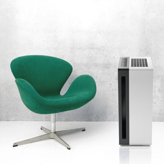 Oczyszczacz Ideal AP 60 PRO stoi koło fotela