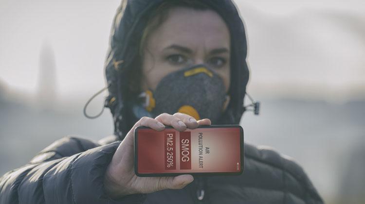 Kobieta trzymająca przed sobą poiomo telefon z uruchomioną aplikacją smogową