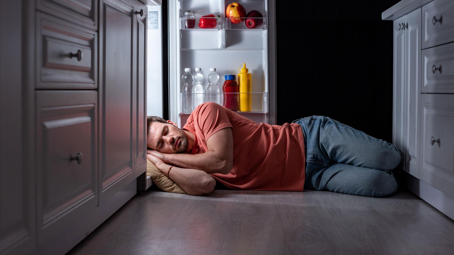 Młody mężczyzna śpi w kuchni z głową w lodówce