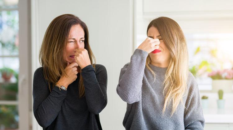 Dwie dojrzałe kobiety patrzą na siebie i ręką zatykają nosy w reakcji na brzydki zapach