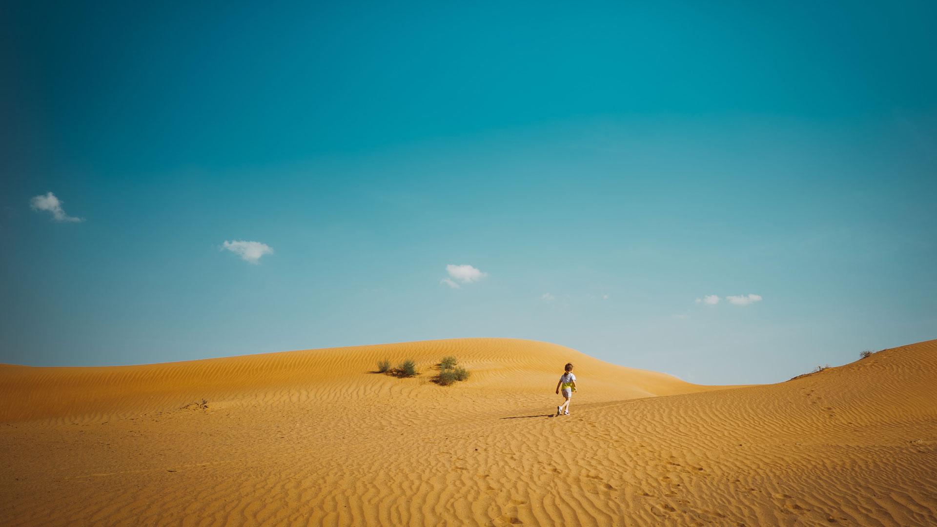 Dziecko idzie przez wydmy na pustyni