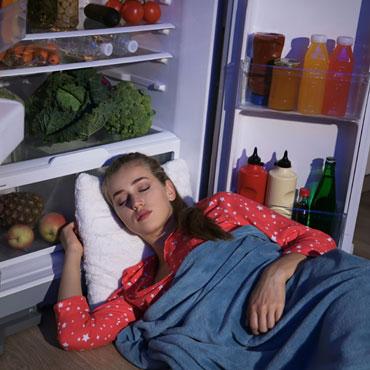 Śpiąca młoda kobieta z głową w otwartej lodówce