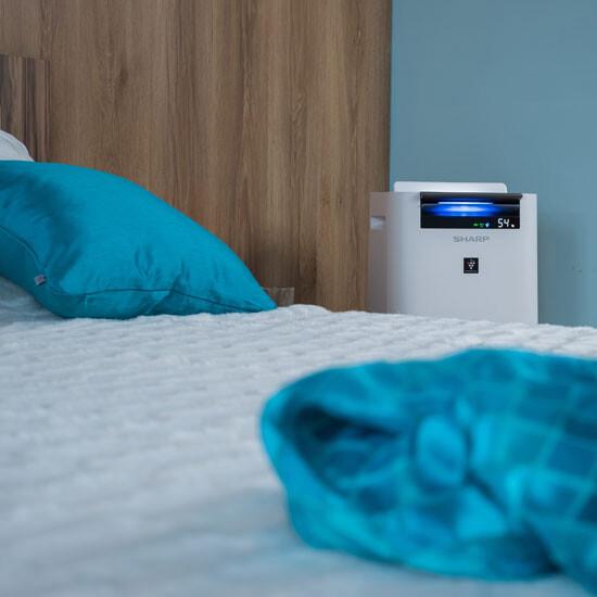 Oczyszczacz SHARP KCG40EUW stoi koło łóżka