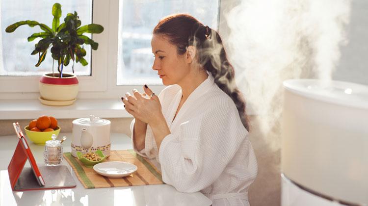 Kobieta w szlafroku siedzi w kuchni. Przed nią tablet oraz dzbanek z herbatą