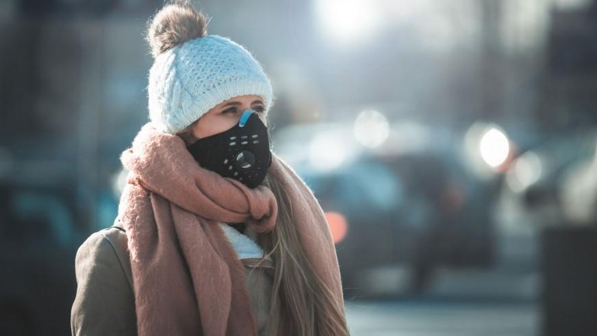 Kobieta stojąca przy ulicy w masce antysmogowej