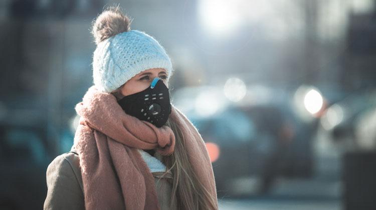 Kobieta ubrana w czapkę i ciepły płaszcz w czarnej masce tlenowej; w tle zakorkowana ulica