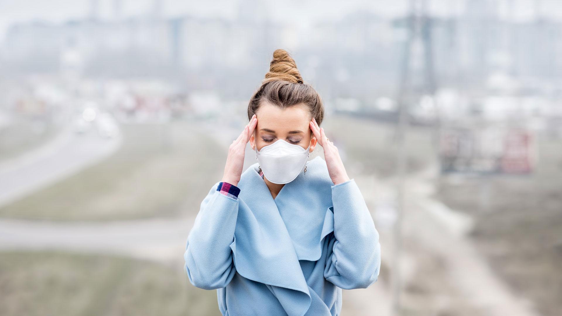 Kobieta w masce smogowej trzyma się palcami za skronie