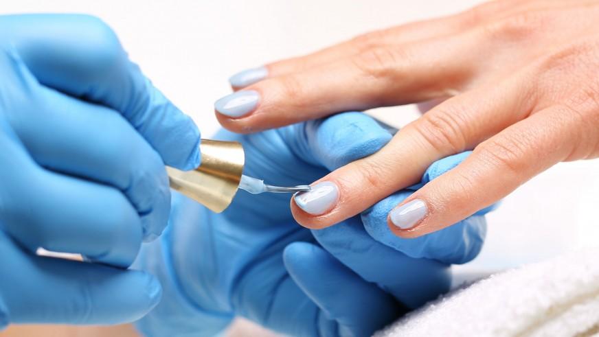 Kosmetyczka w rękawiczkach nakłada niebieski lakier na paznokcie klientki