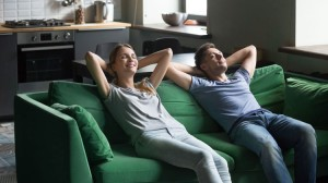Młoda para odpoczywa na zielonej sofie. W tle aneks kuchenny