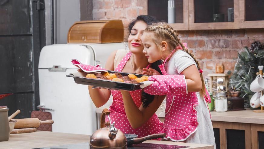 Mama z córką w kuchni wąchają świeżo upieczone ciasteczka położone na blasze
