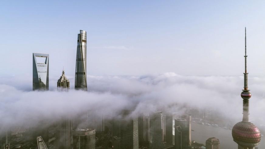 Widok z lotu ptaka na centrum miasta - wieżowce. Budynki pokrywają gęste chmury przez które wybijają się tylko wieże dwóch najwyższych konstrukcji.